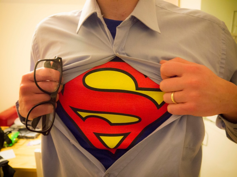 Man pulling open his shirt to reveal superman logo